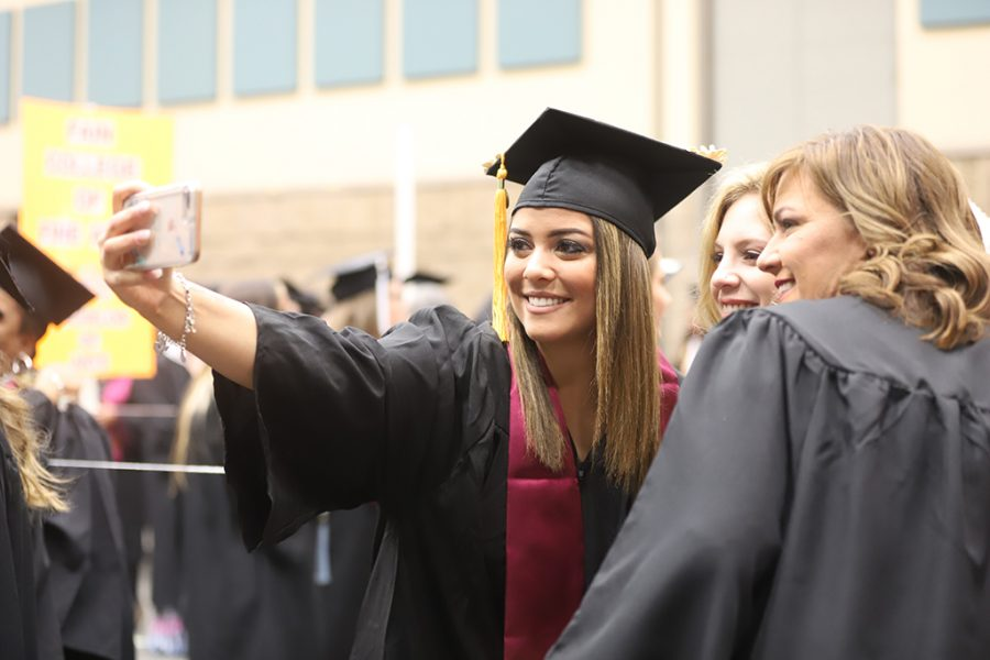 Haleigh Camerlin, nursing, smiles and poses as she takes a selfie with friends before the graduation ceremony on Dec. 15.
