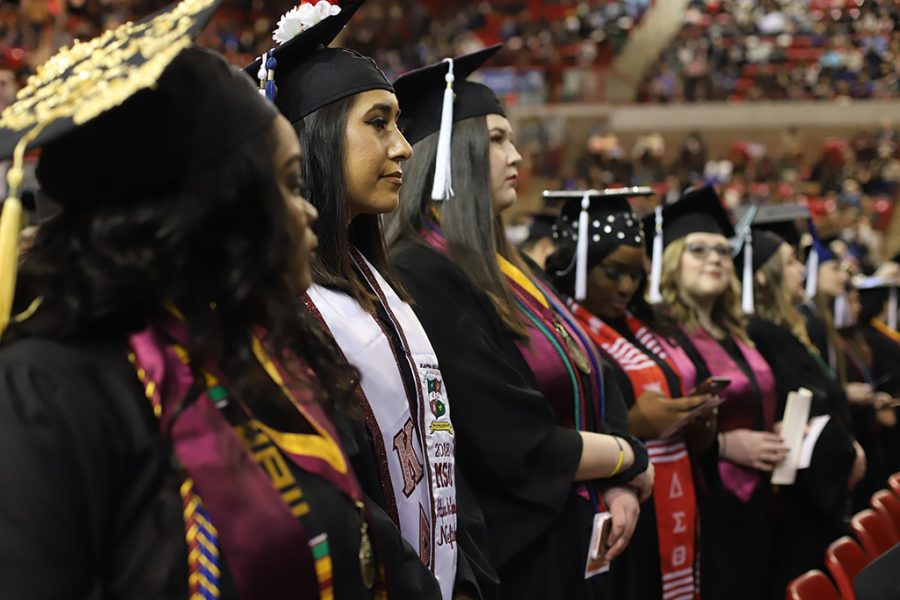 Graduates stand and listen as they wait for the graduation ceremony to begin on Dec. 15.