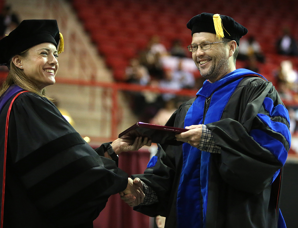 Chris+Hansen%2C+associate+professor+of+chemistry%2C+receives+the+Faculty+Award+from+Laura+Fidelie+at+Midwestern+State+University+graduation+Dec.+15%2C+2018.+Photo+by+Bradley+Wilson