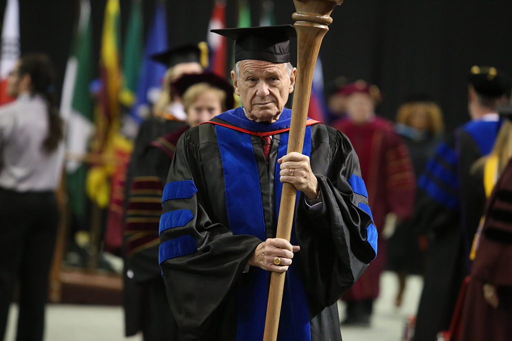 Harry+P.+Hewitt%2C+professor+and+chair+of+the+history+department%2C+leads+the+faculty+out+of+graduation+at+Midwestern+State+University+graduation+Dec.+15%2C+2018.+Hewitt+is+retiring+as+the+longest-serving+faculty+after+51+years.+Photo+by+Bradley+Wilson