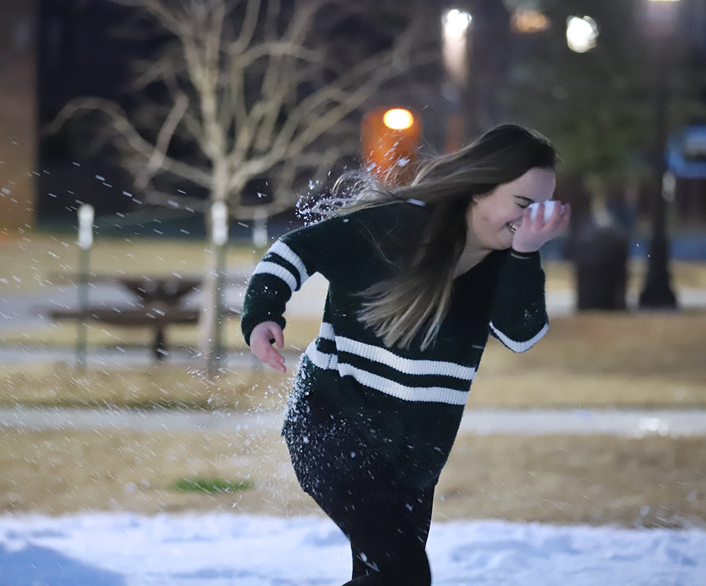 Dental Hydgiene freshman Lauren Cox tries to runaway from an incoming snowball, whilst eating her own snowball at the 'Dashing through the snow' event hosted by UPB and The Bridge. Jan 14. Photo by Bridget Reilly
