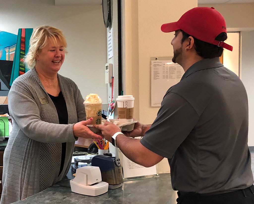 Manny Bhogal, Chartwells marketing specialist, delivers drinks to Cynthia Cummings, special events coordinator, in Clark Student Center.
