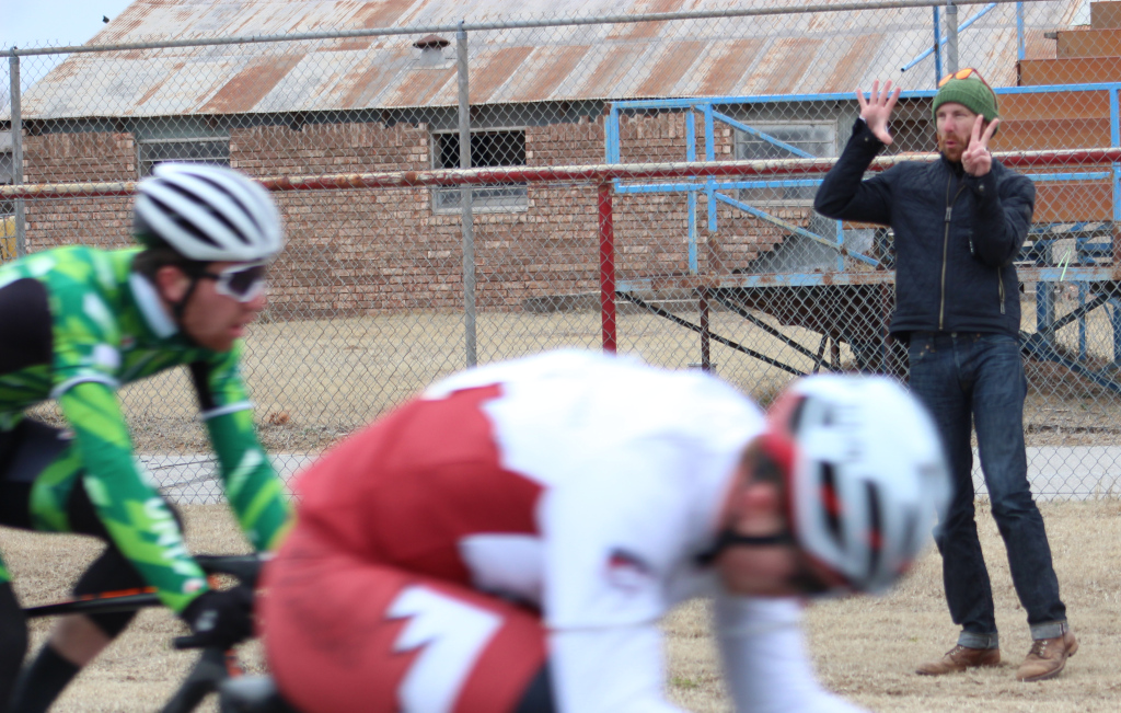 Cycling+director+Charlie+Zamastil+signals+remaining+laps+to+men%27s+%27A%27+team.+Photo+by+Sharome+Burton.+March+10.