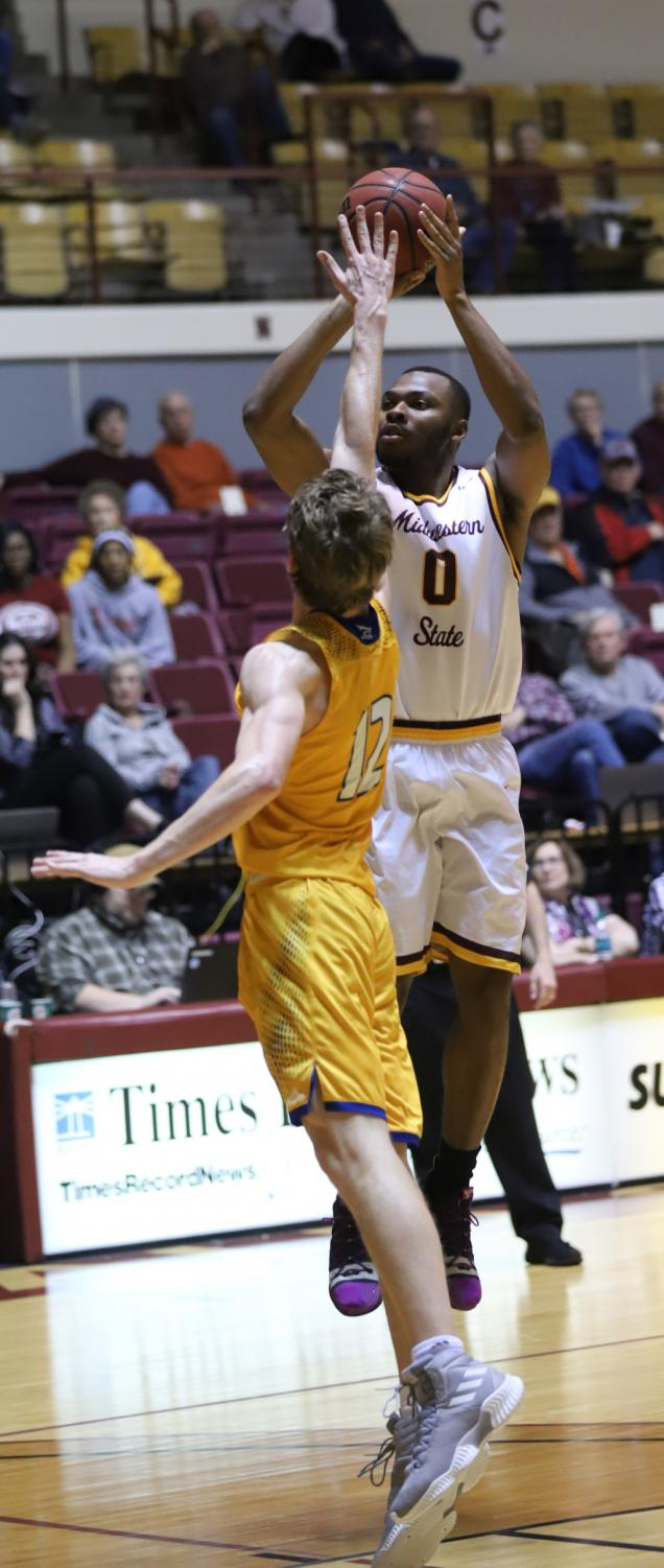 Jajuan+Starks%2C+business+senior+rises+for+contested+jump+shot.++Photo+by+Sharome+Burton.+March+2.