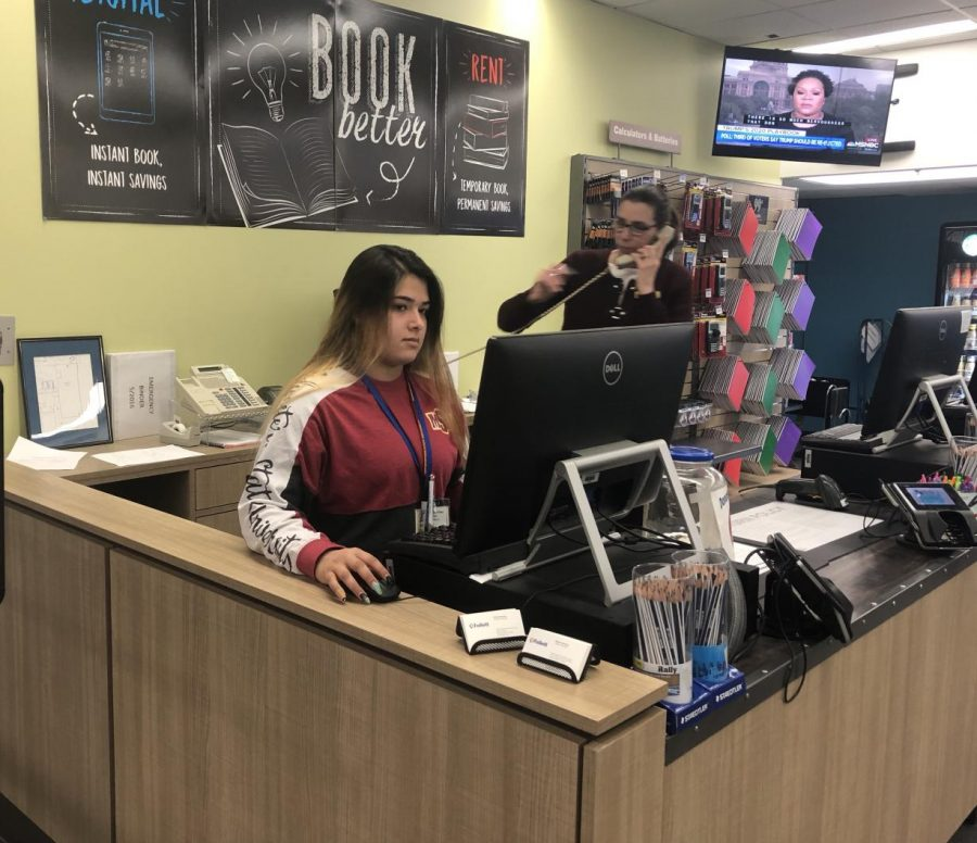 Student worker busy at the campus bookstore.