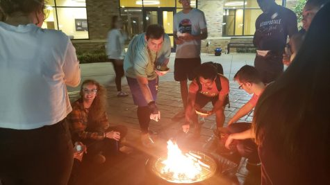 Students surround blazing firepit while roasting marshmellows.