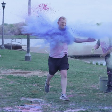 Computer science senior Christian Douglas runs with open arms through the dry paint at the 5Kolor run at Sikes Lake for Wichita Falls Faith Mission. April 2. Photo by Bridget Reilly