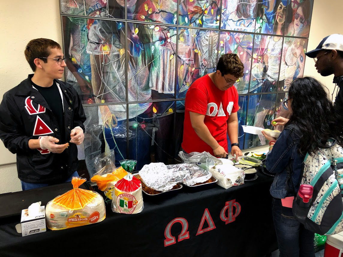 Members of Omega Delta Phi, Christopher Cruz and Michale Gonzales, sell tacos at ODPhajitas event April 24.