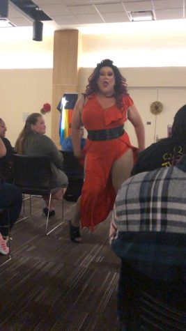 Drag queen in orange dress and black belt dancing down walkway between audience members