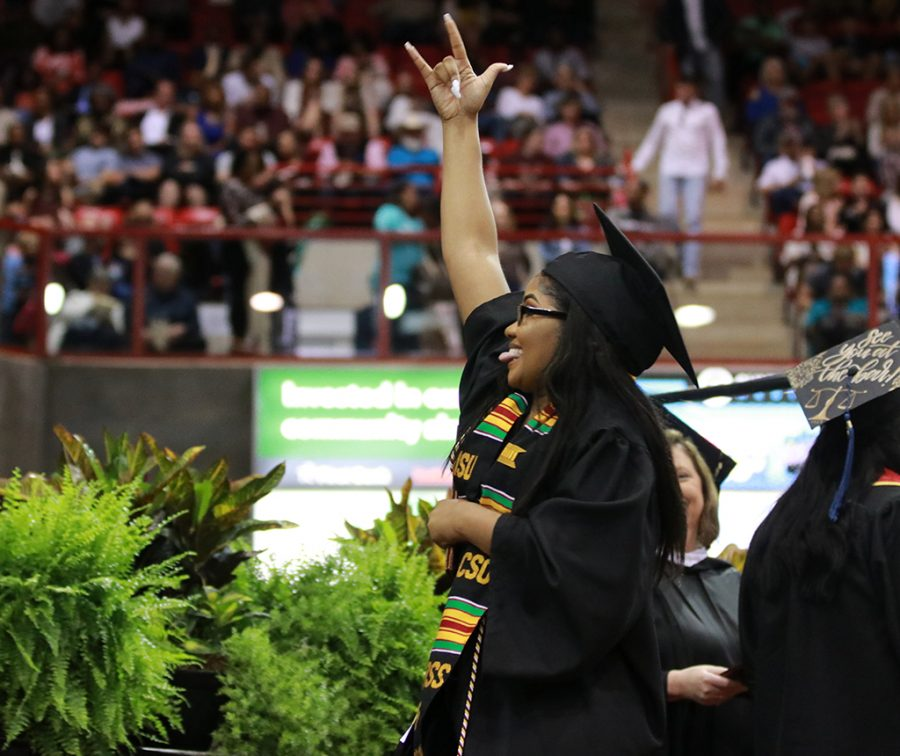 Biology graduate Tarrant Miller celebrates getting her degree with friends and family in the crowd as she walks across the stage at the graduation ceremony at Kay Yeager Coliseum on May 11.