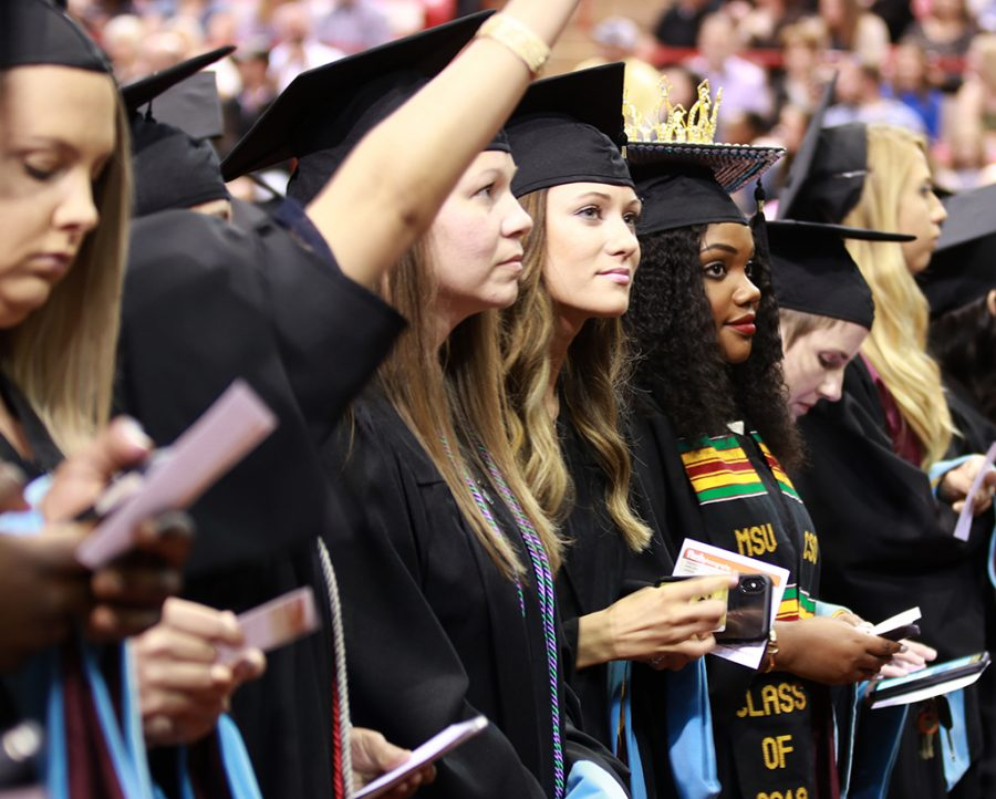 Seniors stand to perpare themselves to walk the stage at the graduation ceremony at Kay Yeager Coliseum on May 11.