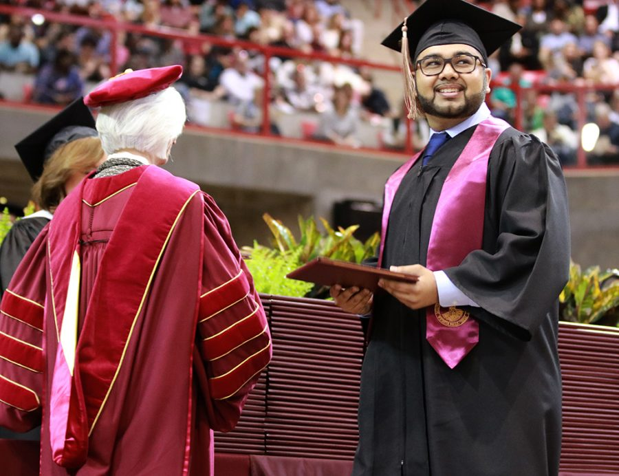 Finance graduate Rahul Vivek Joshi smiles big with his degree as he walks across the stage at the graduation ceremony at Kay Yeager Coliseum on May 11.