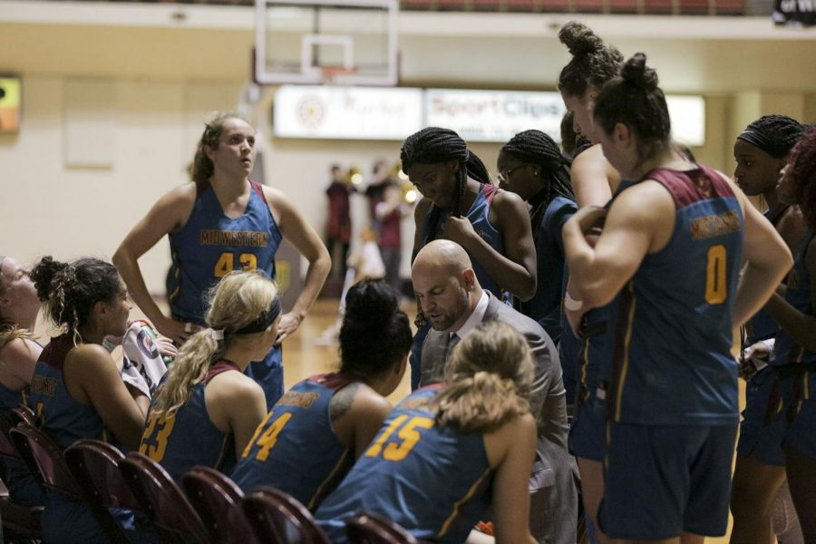 Coach Reay sits down with the women's basketball team in between plays. Feb. 13. Photo by Colin Stevenson.