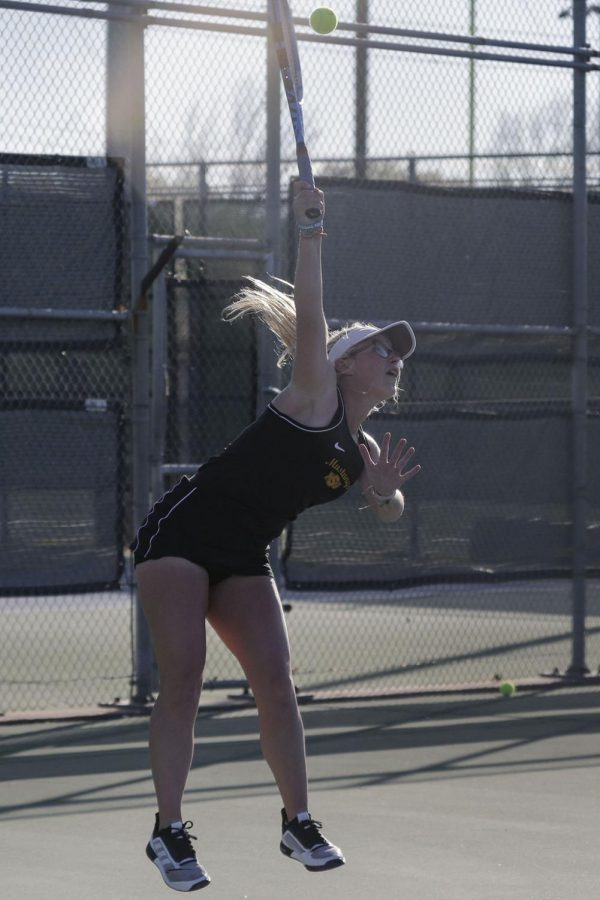 asie Curry serves in her doubles match
