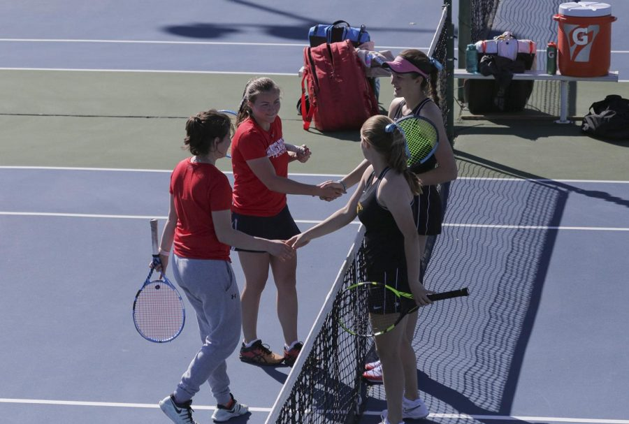 Senior Juliette Mary and pre-med freshman Emilija Visic shake hands with their opponents after a victorious doubles game
