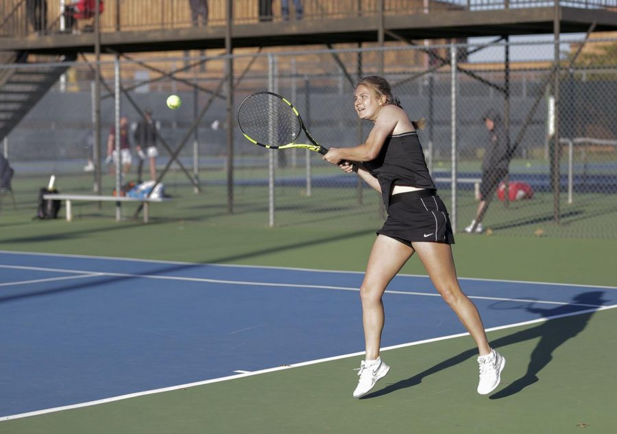 Juliette Mary watches the ball after her backhand hit