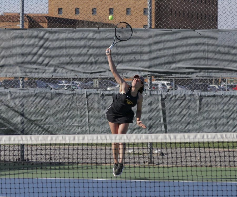 lobal studies senior Lea Cizeron serves in her singles match