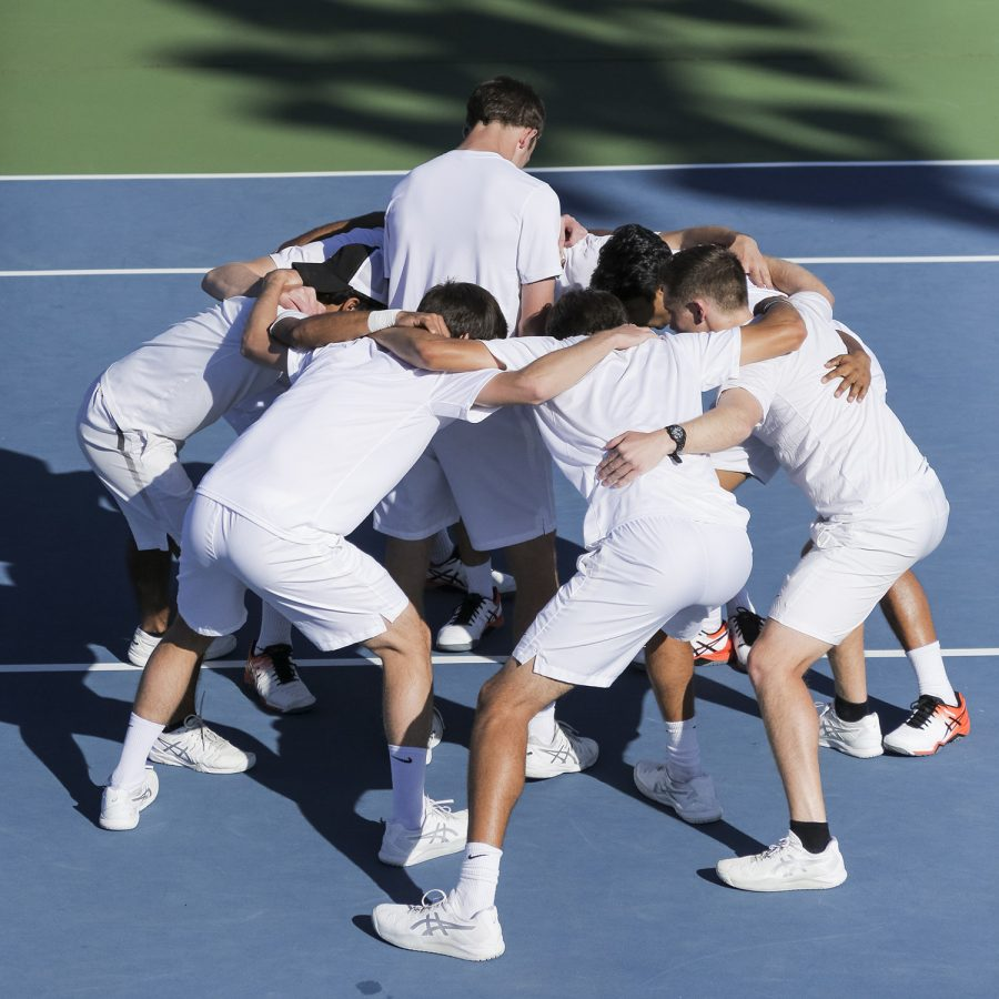 The men's tennis team players perform a pregame group chant