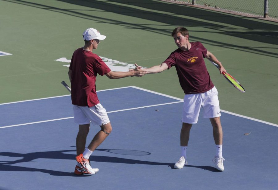 Mechanical engineering junior Alex Martinez Roca high-fives with general business freshman Alexandre Crepy after winning a point in their doubles match