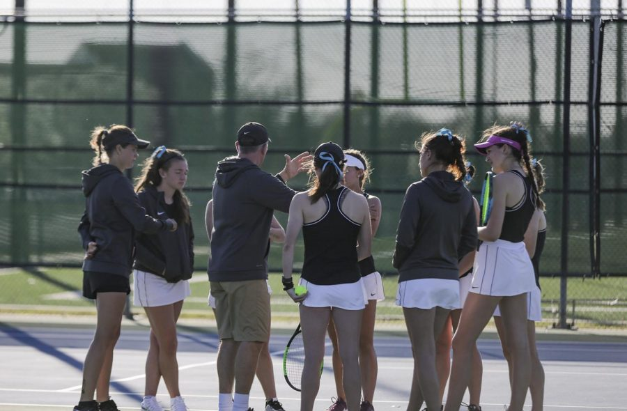 Head coach Scott Linn talks with the women's team after their doubles matches