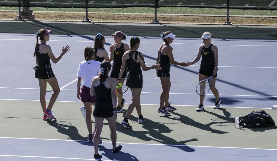 The women's team congratulates teammates global studies senior Lea Cizeron and kinesiology sophomore Casie Curry after their successful doubles match