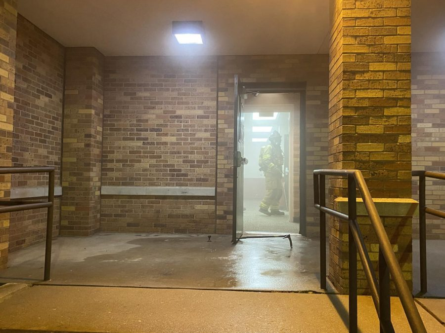Firefighter looks out of Pierce Hall exit door while clearing smoke.