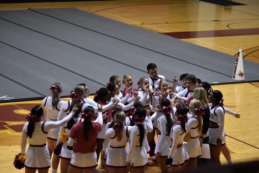 MSU Cheer huddled up together.