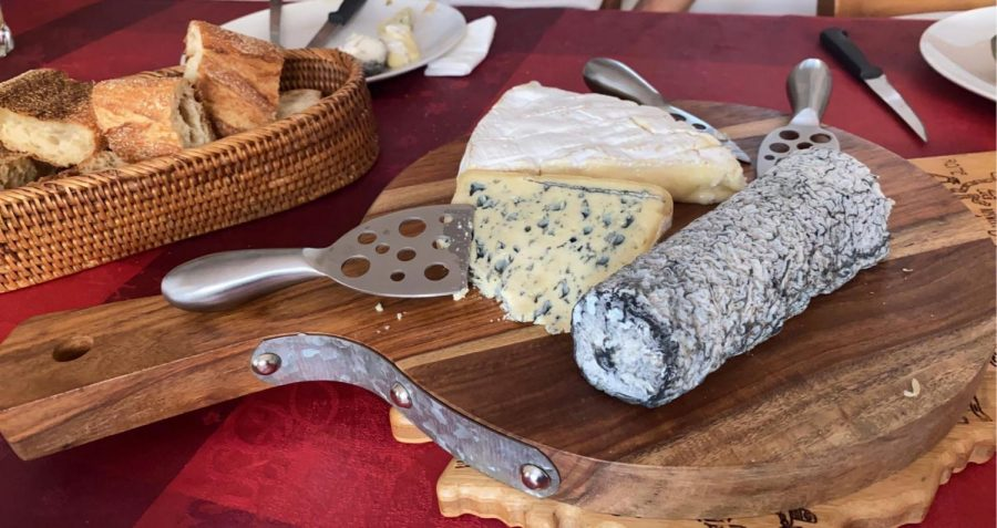 Three types of French cheese sit on a platter, ready to be eaten
