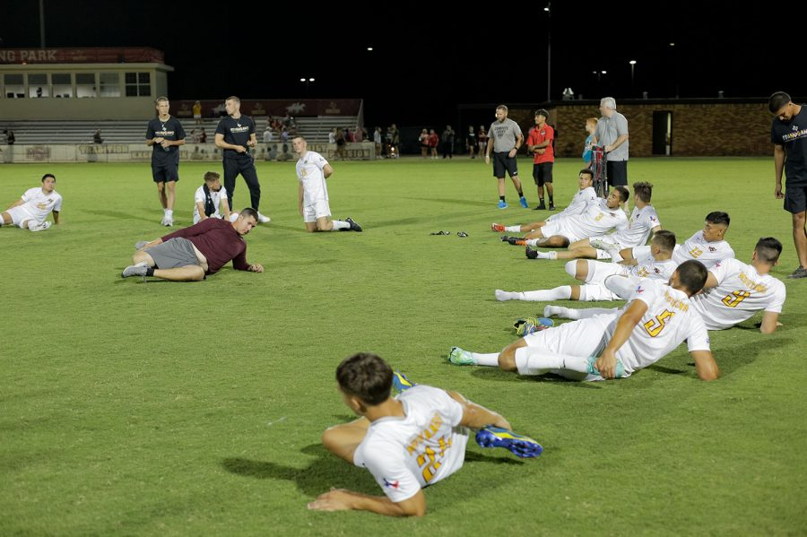 Graduate assistant strength and conditioning coach John Burke leads players in stretches after their win against Northeastern State