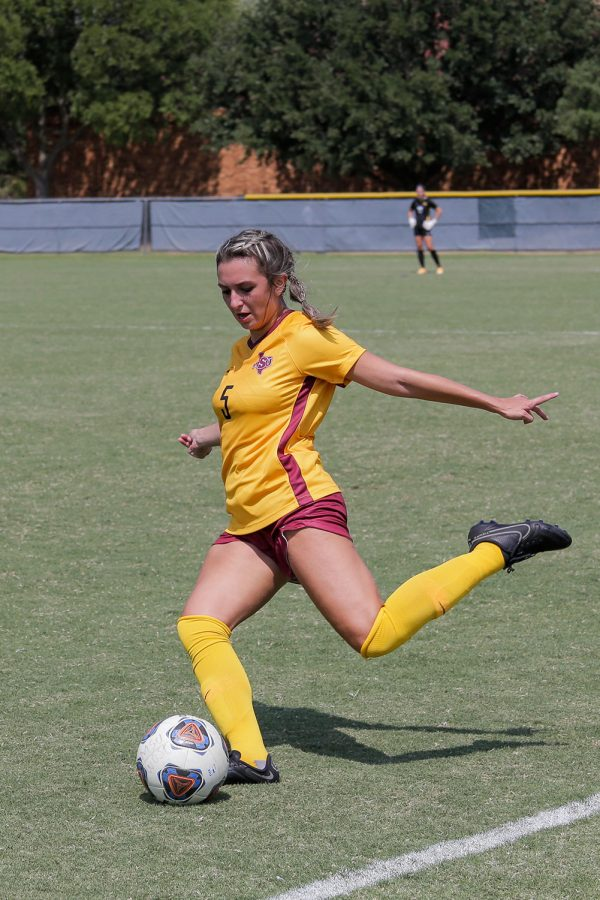 Biology junior and midfielder Alyssa Salinas rears her leg to pass the ball to a teammate downfield