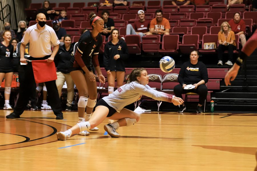 Undecided freshman and libero Amy Dewalt recieves as the opponent hits a sharp cross spike