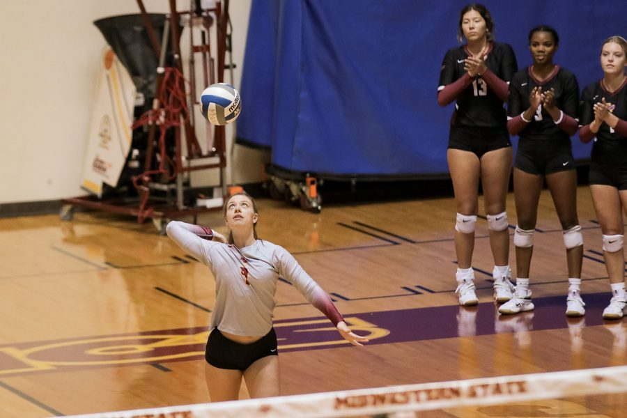 Undecided freshman and libero Amy Dewalt winds up for a serve as her teammates clap to encourage her