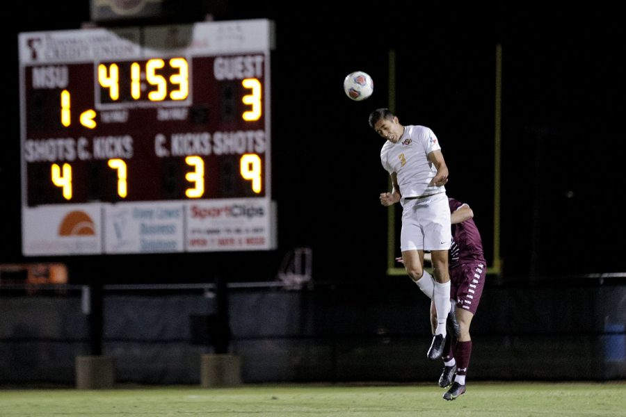 Finance senior and defender Carlos Vargas heads the ball to keep it away from his team's goal