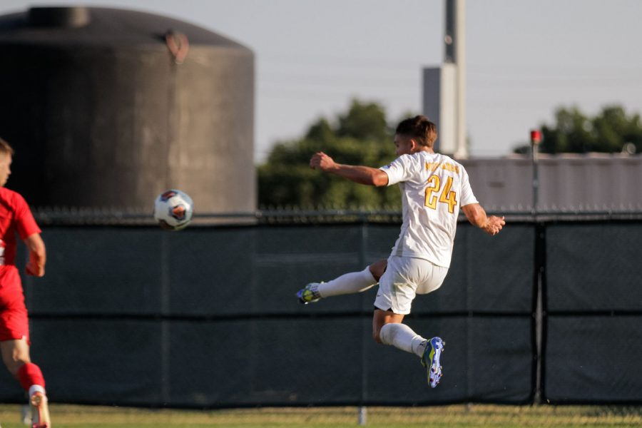 Exercise physiology and midfielder Colby Parton leaps and sends the ball closer to opposing Simon Frasers goal.