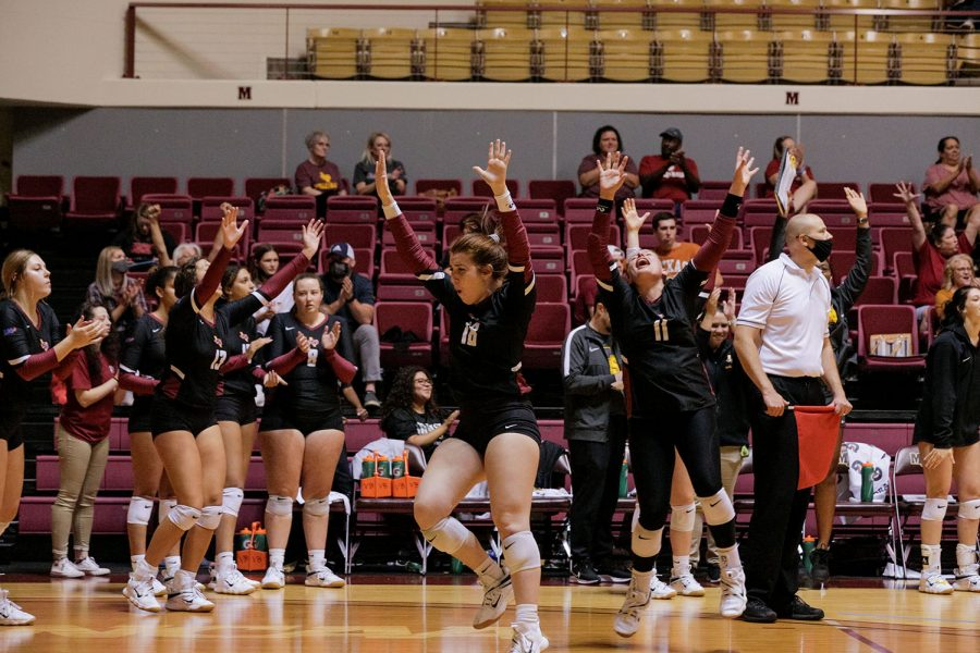 Education freshman and defensive specialist Delaney Torres and sports and leisure studies sophomore Autumn Roach celebrate with their teammates over a scored point by the Stangs