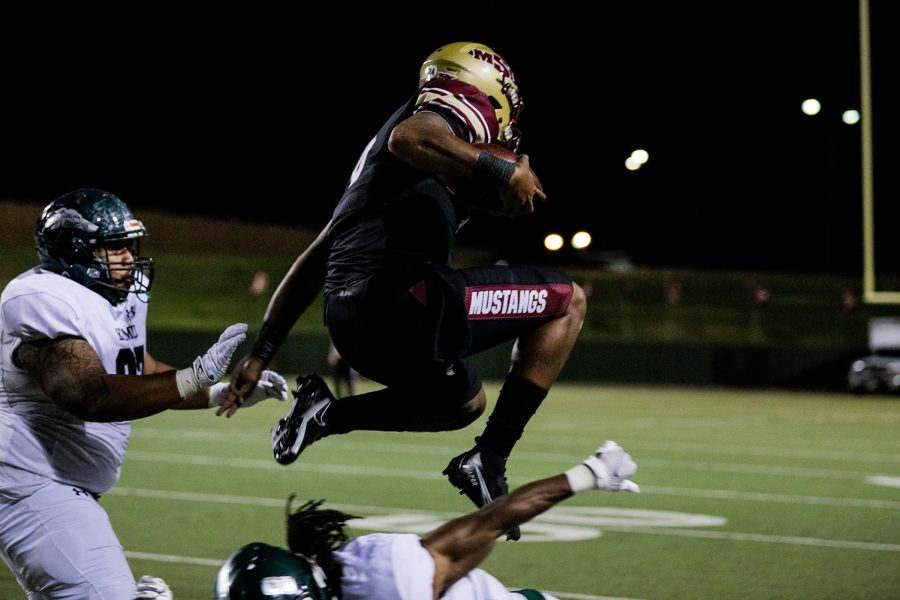 Masters of sports administration senior and quarterback Dillon Sterling-Cole leaps over an opposing Eastern New Mexico player to dodge his attempt at a tackle