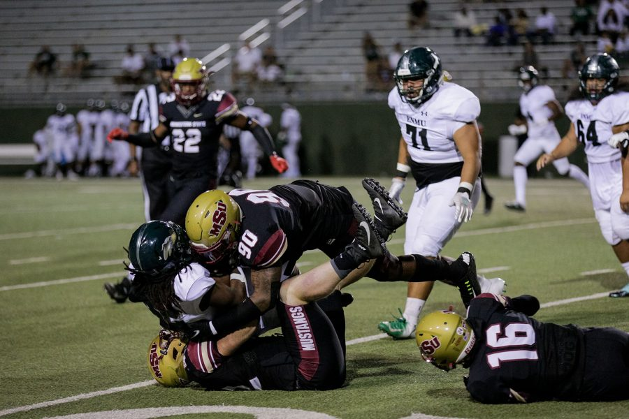 Applied arts and sciences and linebacker Zack West and sports and leisure junior and defensive lineman Zed Asowata tackle an opposing Eastern New Mexico player