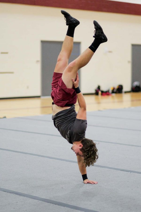 Kinesiology and english senior Danlee Duncan performs a one-handed handstand during cheerleading practice.