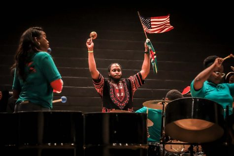 Mecahnical engineering junior Garvin Joseph holds up flags as the Black Steel pan group performs.