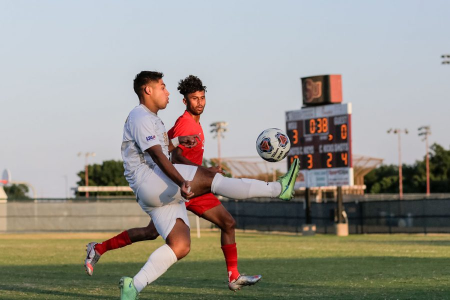 To intercept the ball, kinesiology sophomore and midfielder Jasub Flores kicks up in the air, preventing a Simon Fraser player from reaching the ball.
