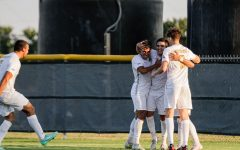 Teammates crowd around kinesiology senior and midfielder Julian Barajas after he made the third goal of the game against Simon Fraser.