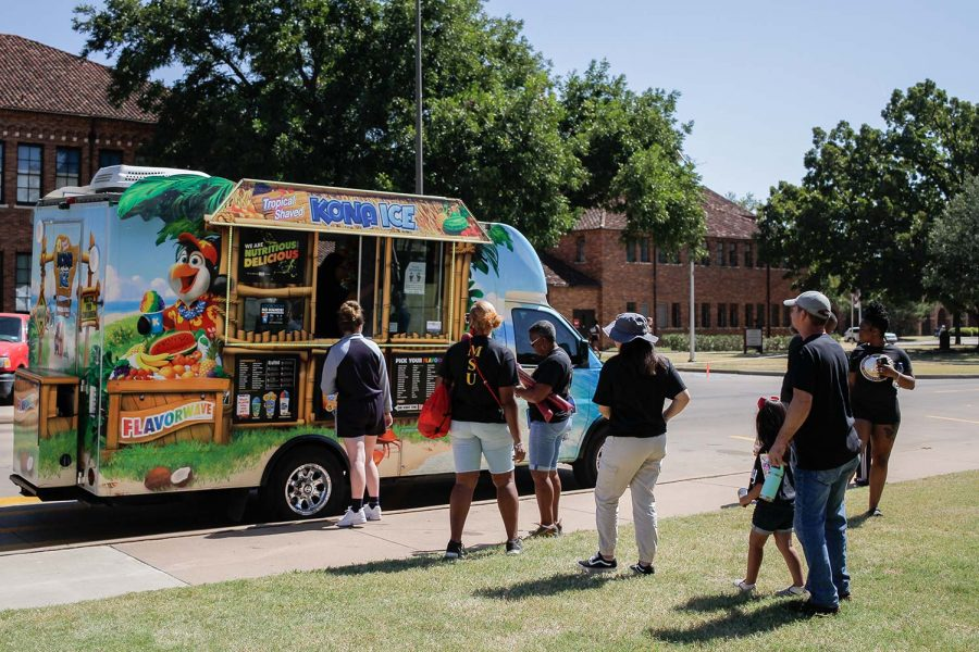 Students and their families line up at a Kona Ice truck.