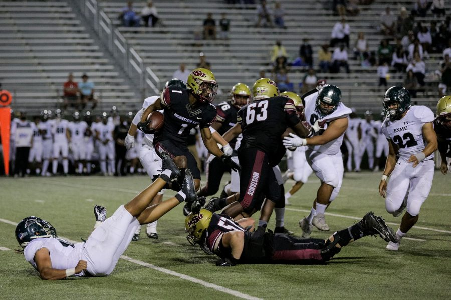 Kinesiology senior and running back KVonte Jackson leaps over an opposing player and masters of sports administration senior, offensive lineman and teammate Austan Davis