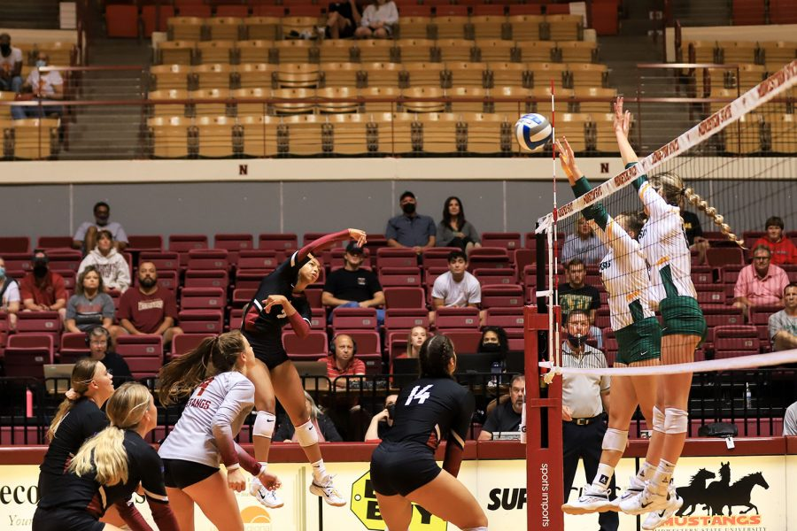 Chemistry sophomore and outside hitter Lauryn Bourne leaps to send an attack across the net to Arkansas Tech