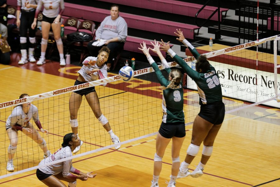 Chemistry sophomore and outside hitter Lauryn Bourne spikes the ball around a block set up by Eastern New Mexico