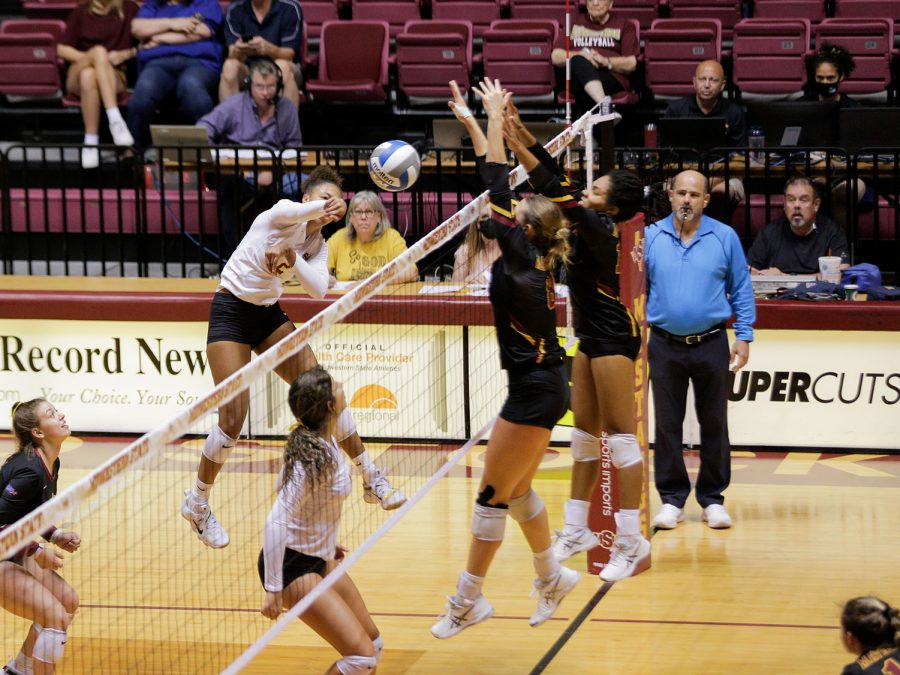 Chemistry sophomore and outside hitter Lauryn Bourne spikes the ball past an attempted block by Colorado Mesa players