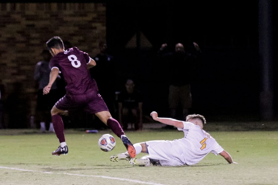 Masters of business administration and defender Nathan Clifford slides to kick the ball out from an opposing players feet