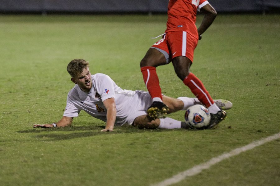 Masters of business administration senior and defender Nathan Clifford dives to kick the ball out from under the feet of a Rogers State
