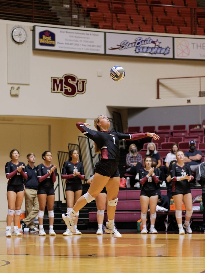 Business freshman and setter Regan Willms serves as her team claps to encourage her