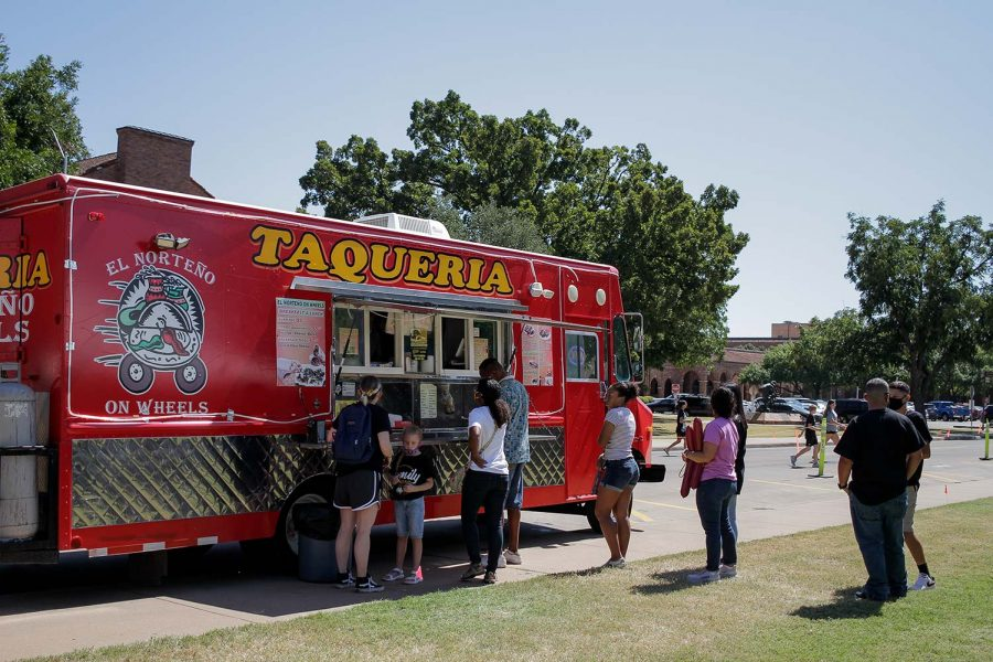 Students and their families line up at a taqueria food truck.